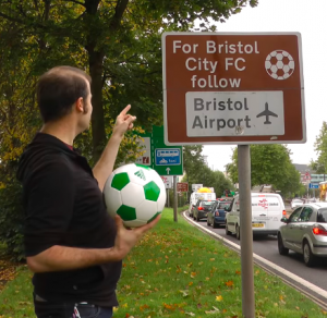 Matt holding a football and pointing at the offending sign