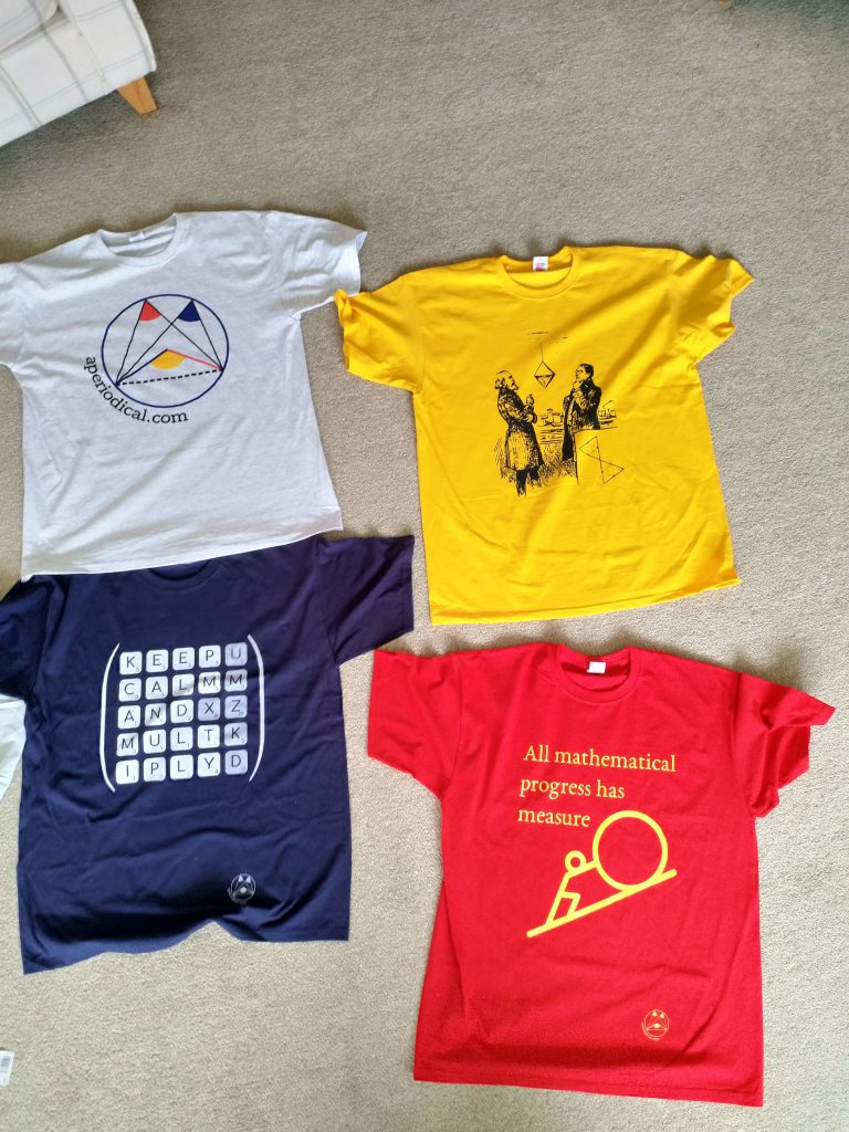 "Four t-shirts laid out on the floor. Clockwise: the aperiodical logo; two men considering an octahedron; ""all mathematical progress has measure zero""; keep calm and multiply matrix"