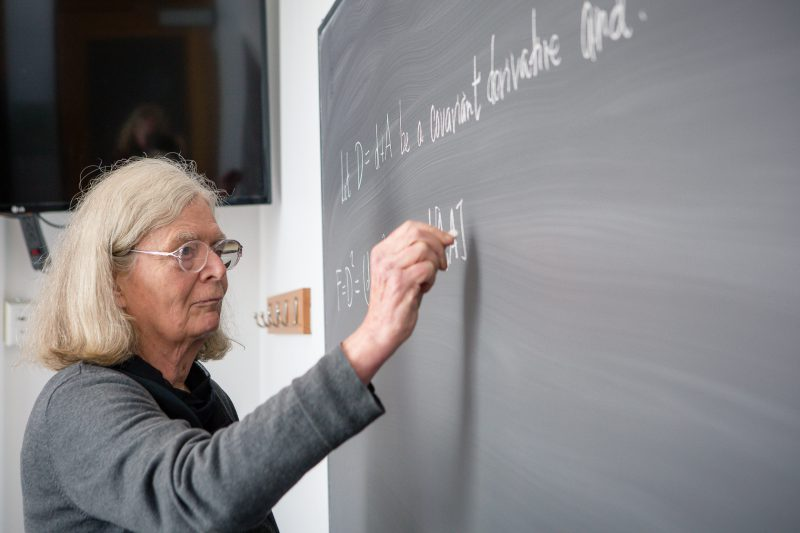 Karen Uhlenbeck writing on a blackboard
