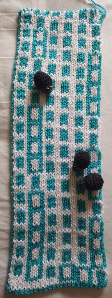 Knitted scarf showing distribution of primes modulo 6 by using coloured blocks in rows of length 6, reverse view