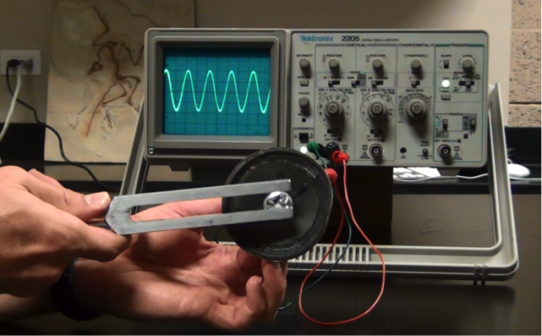 A tuning fork held in front of an oscilloscope, showing a sine wave