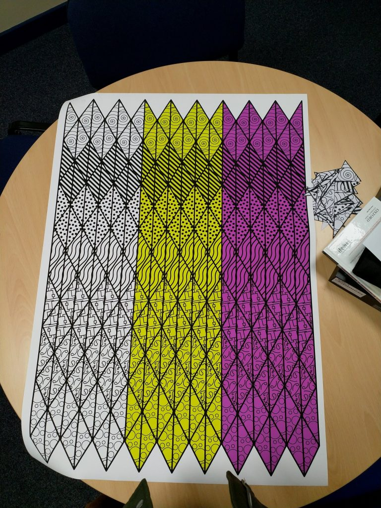 Printed A1 sheet lying on a table. Triangle pieces are arranged in rows. There are six rows each of white, yellow and magenta triangles.