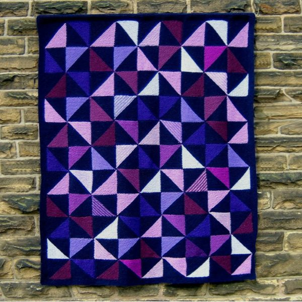 Woollen art hanging on a wall. The picture is made of squares with alternating half-triangles in many different colours