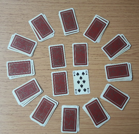 Initial setup of a game of Clock Patience. The face-up card is the 8 of spades