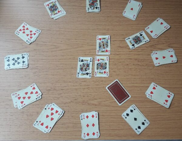 The card at position 2 is revealed to be the king of spades, leaving one card face-down at position 5