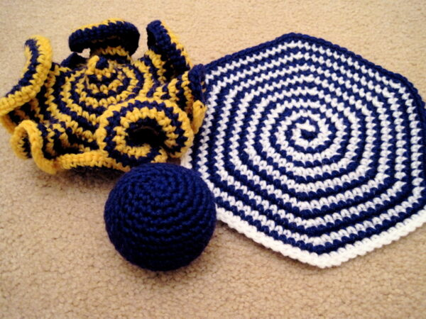 Three crochet objects: a flat hexagon in purple and white; a ball in solid purple; and a curly one in purple and gold