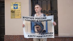 Konstantin Kotov holding a sign with a photo of Azat Miftakhov and a caption in Russian