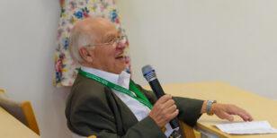 Sir Michael Atiyah holding a microphone