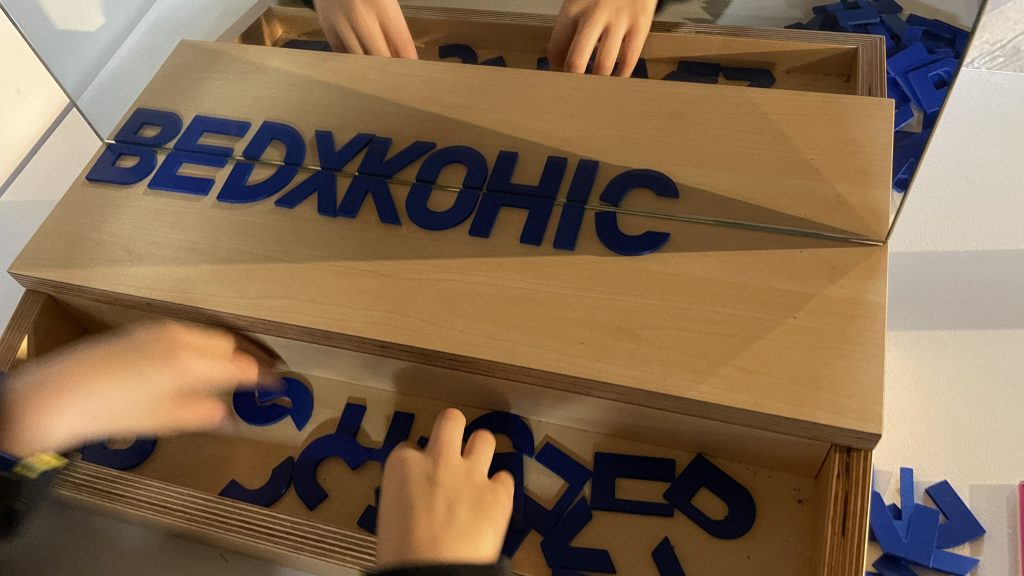 Plastic bottom halves of letters reflected in mirror to form whole letters B E D X K O H I C