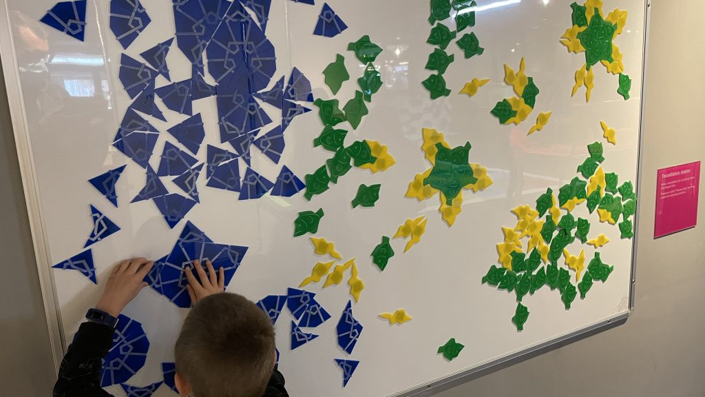 Child playing with magnetic tiles.