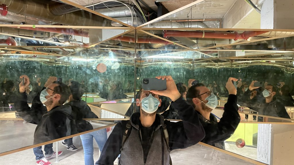 Man enclosed by mirrors taking a picture of his many reflections.